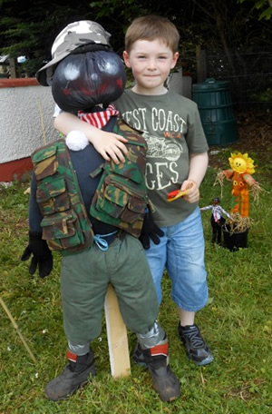 Pupil of St Aidans Ballintrillick School with his arm round his scarecrow