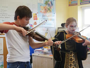 Boy & girl at St Aidans NS Ballintrillick playing fiddle