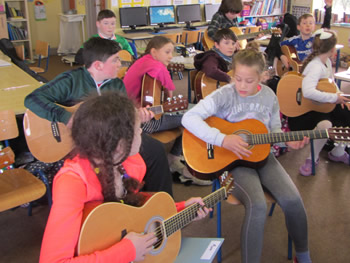 Children at St Aidans School playing the guitar