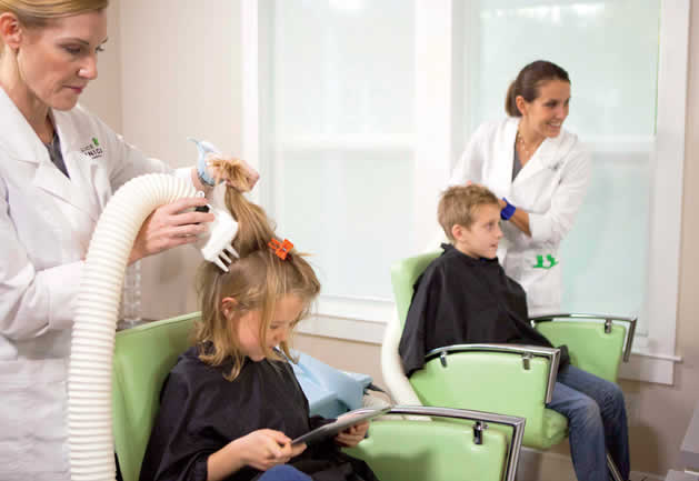 Lady treating headlice on child