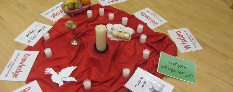 Red cloth with candles around and white paper angel